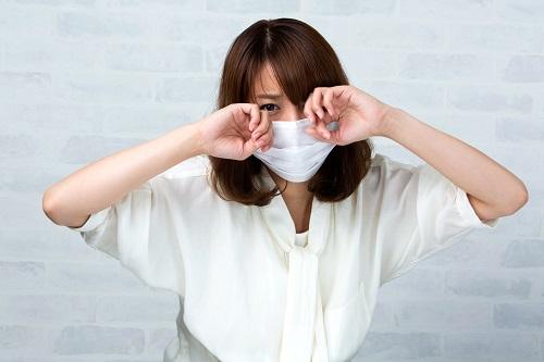 猫アレルギーで目をこする女性